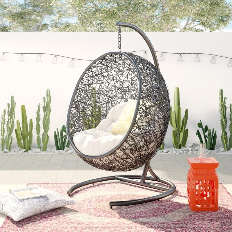An outdoor chair shaped like an egg with a white cushion on a rug