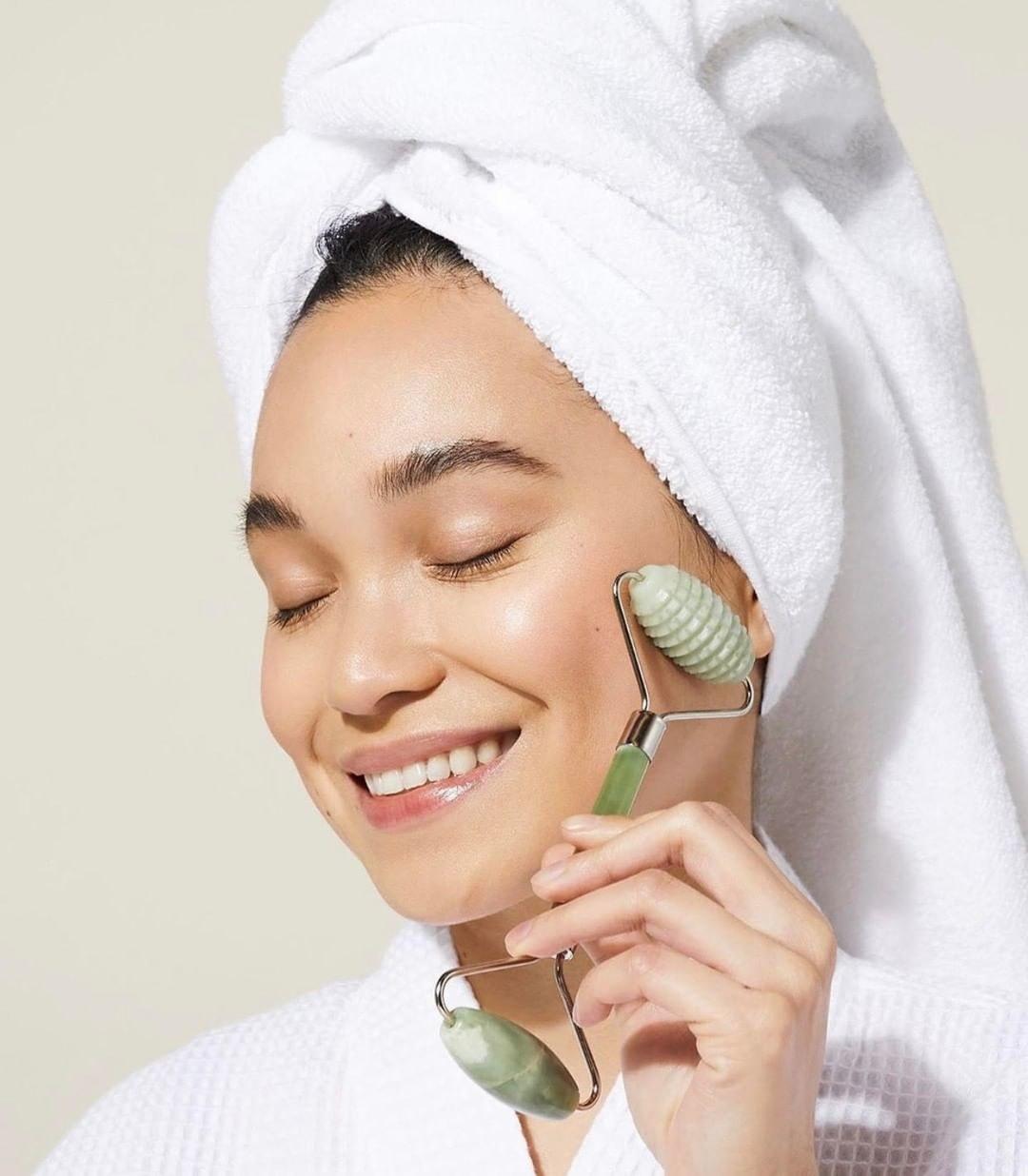 A person placing a jade facial roller against their cheek