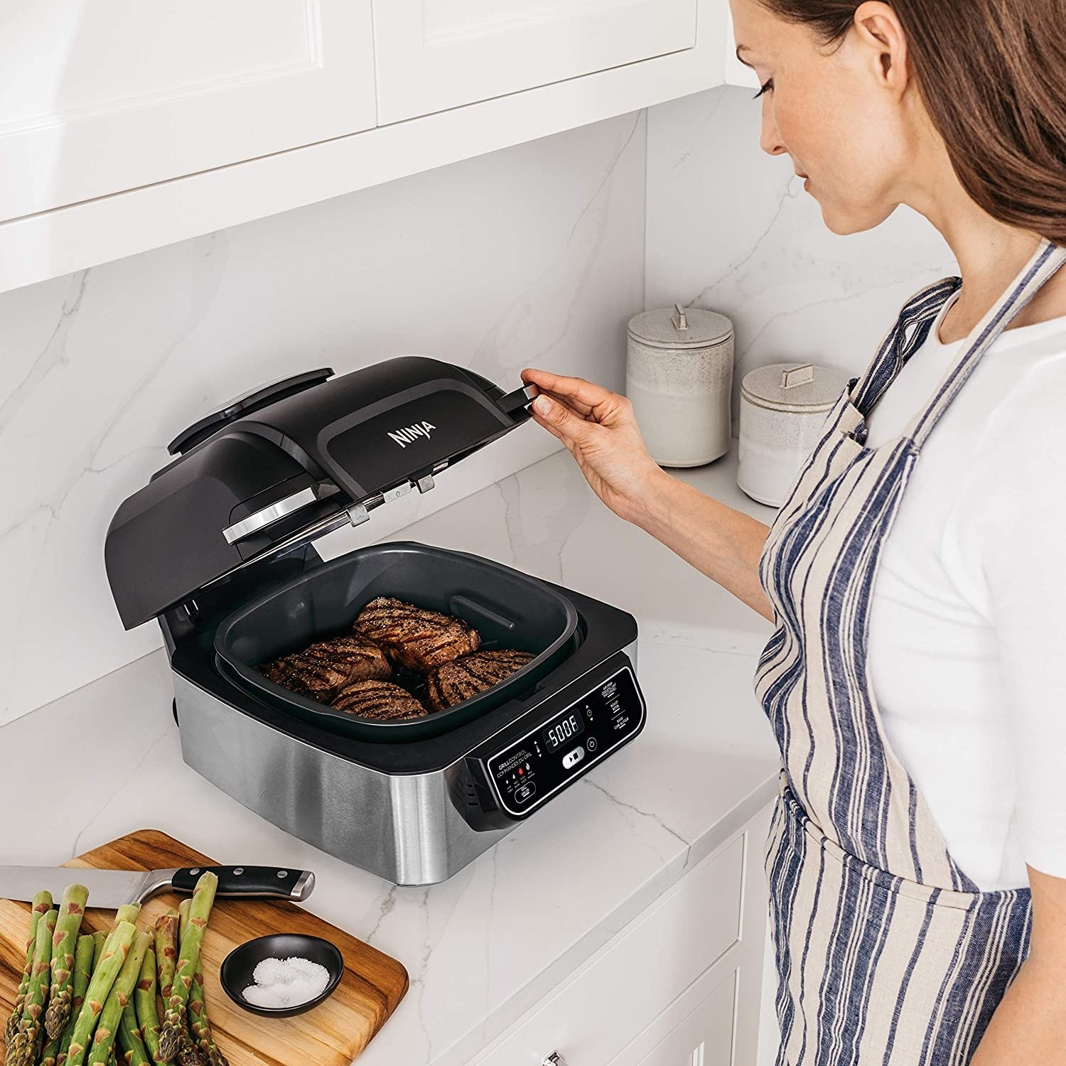 A NInji foodie grill with steaks cooking in it