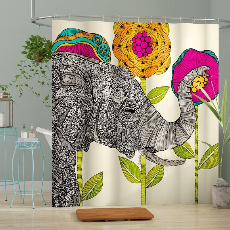 A colorful shower curtain with a giant elephant and flowers on it