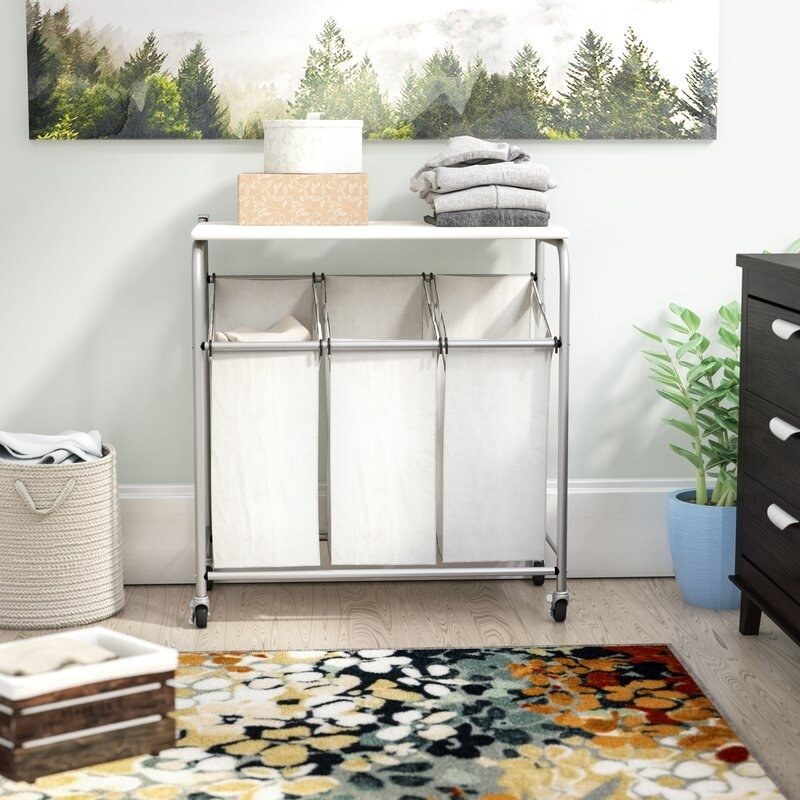 A white rolling laundry hamper with a steel frame and wheels inside a bedroom