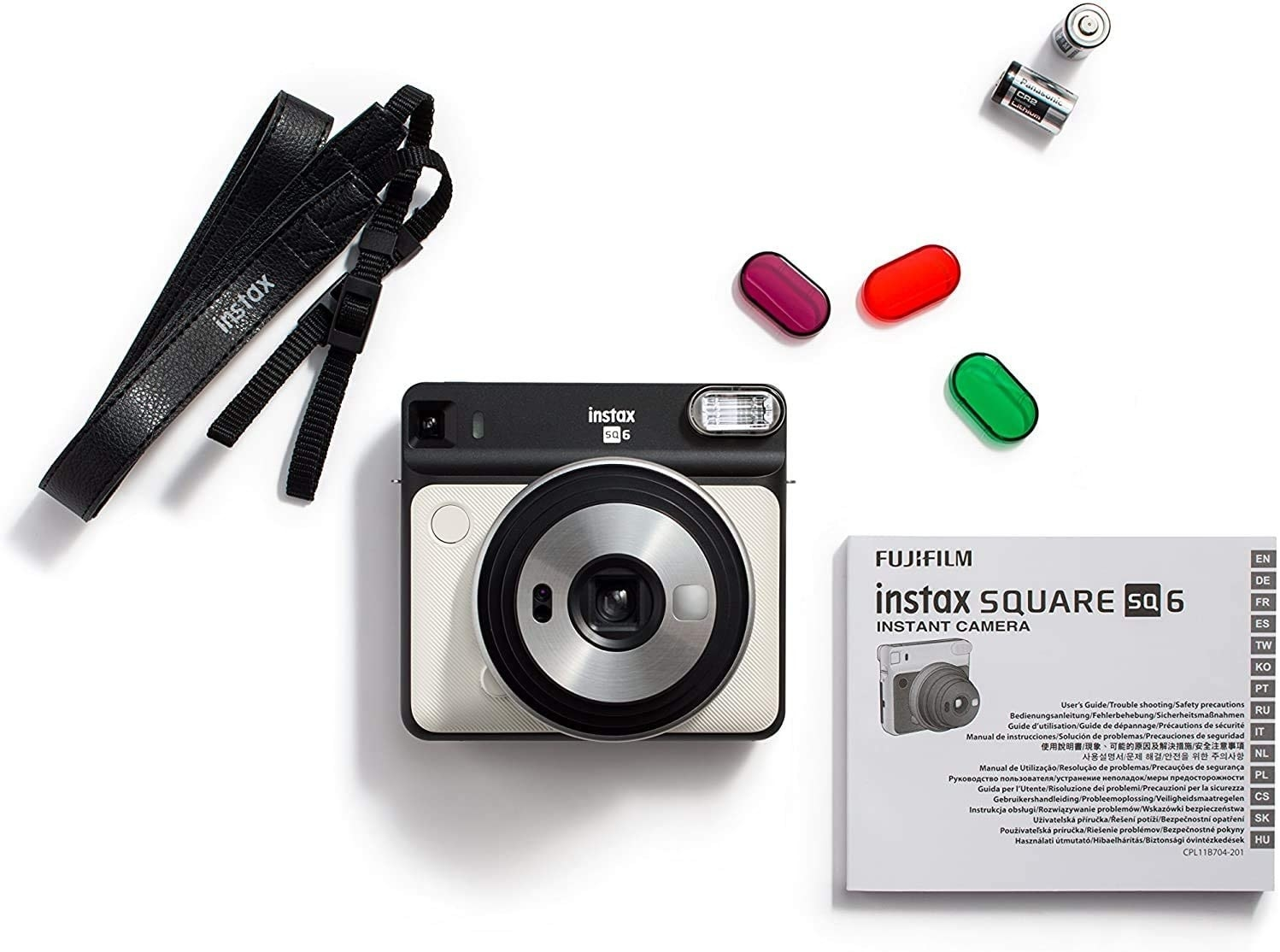 A small instant camera on a plain background with a strap and manual booklet beside it