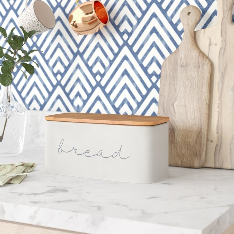 White bread box with wooden lid on kitchen counter