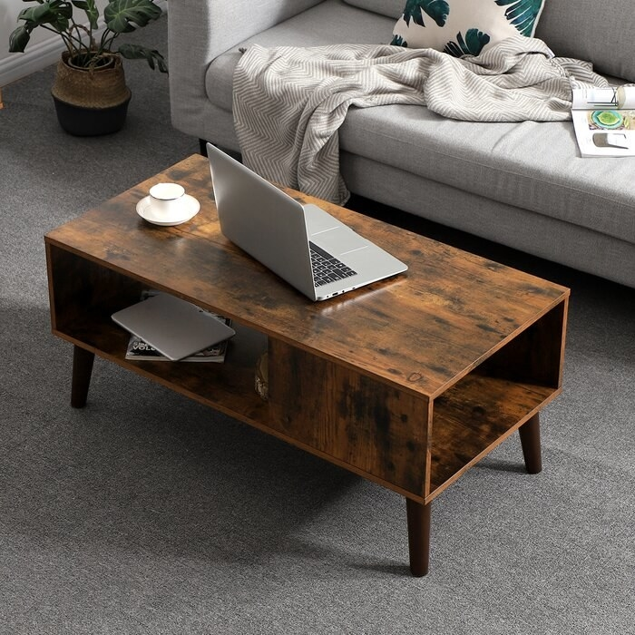 wooden retro-looking coffee table with laptop on top