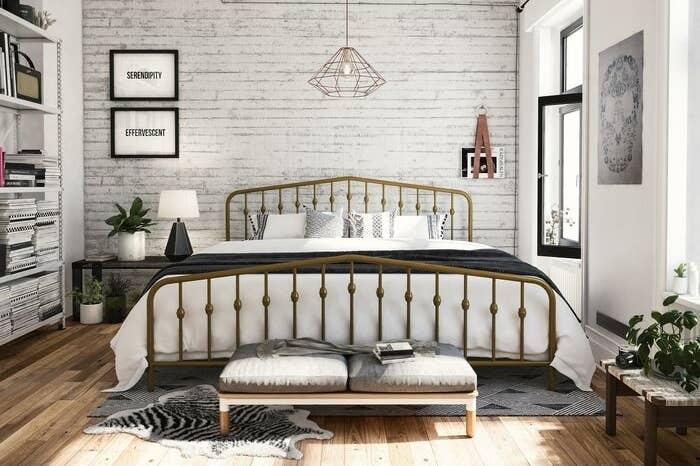 gold metal bed frame in a light-filled bedroom