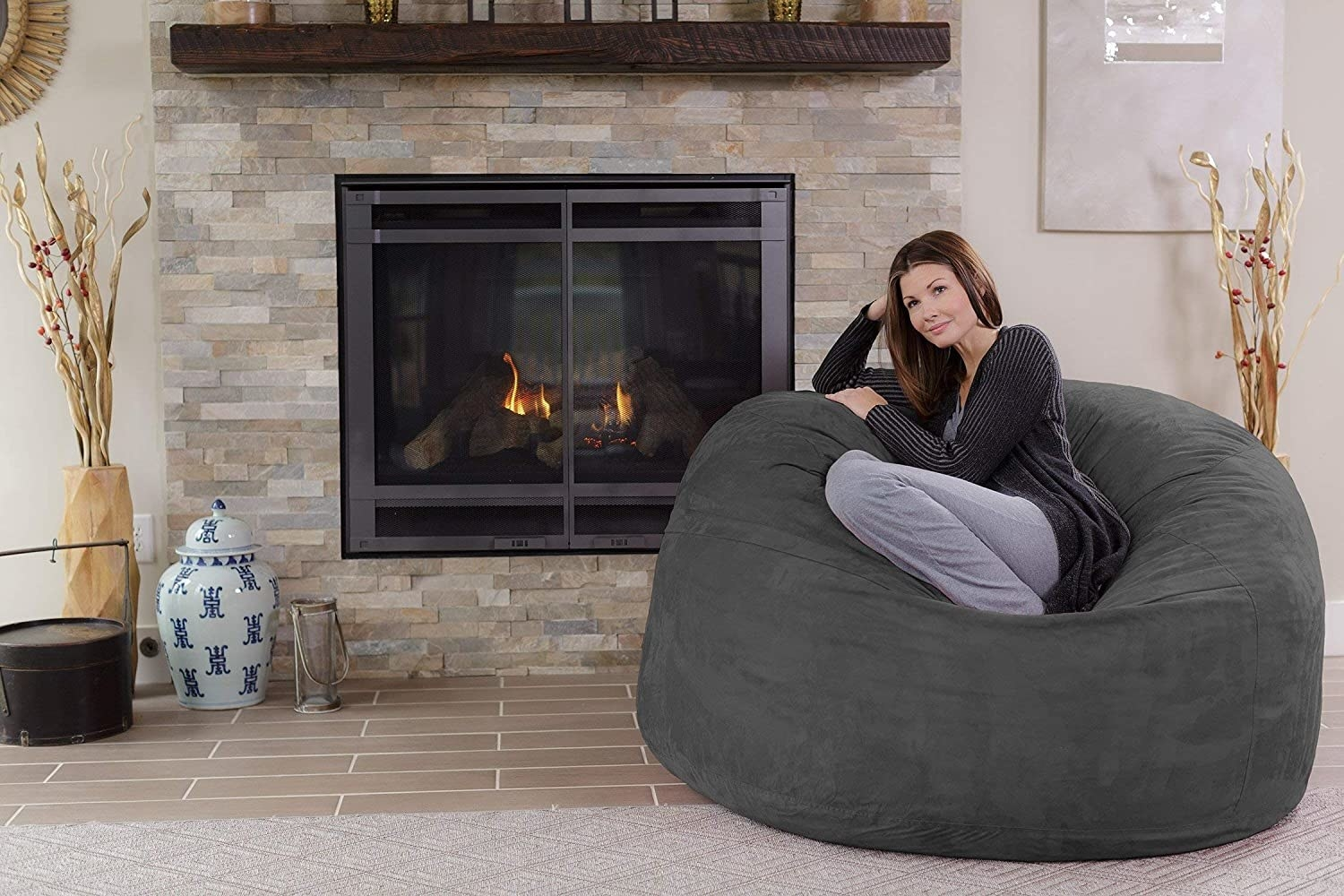 A person sitting in the bean bag chair by a fireplace