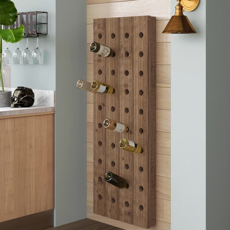 A wine holder that looks like a wooden wall with holes