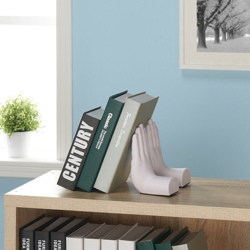 A couple of bookends holding up a book that look like hands