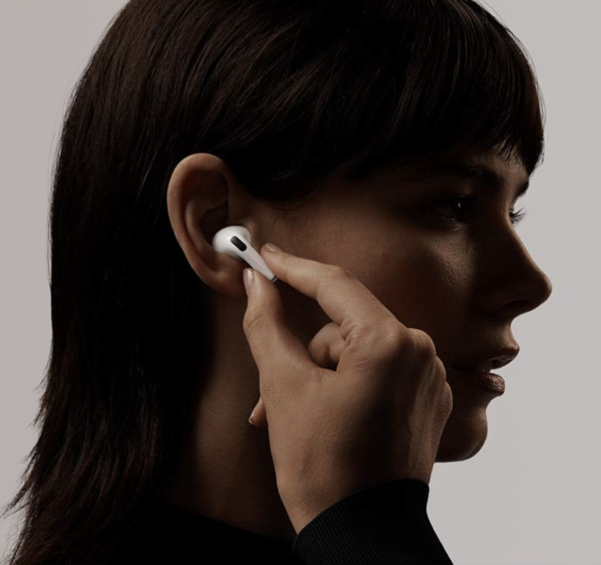 Model putting white AIrPods Pro earbud into ear