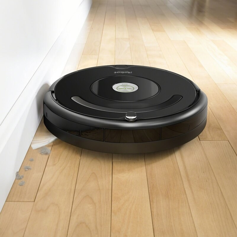 A black robot vacuum sucking up dirt on hardwood floor