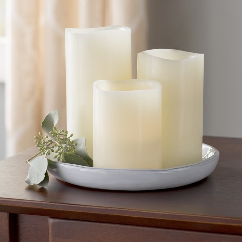 Three flameless candles on a dish on a table