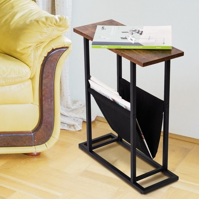 thin end table with wooden top and black magazine storage at the bottom