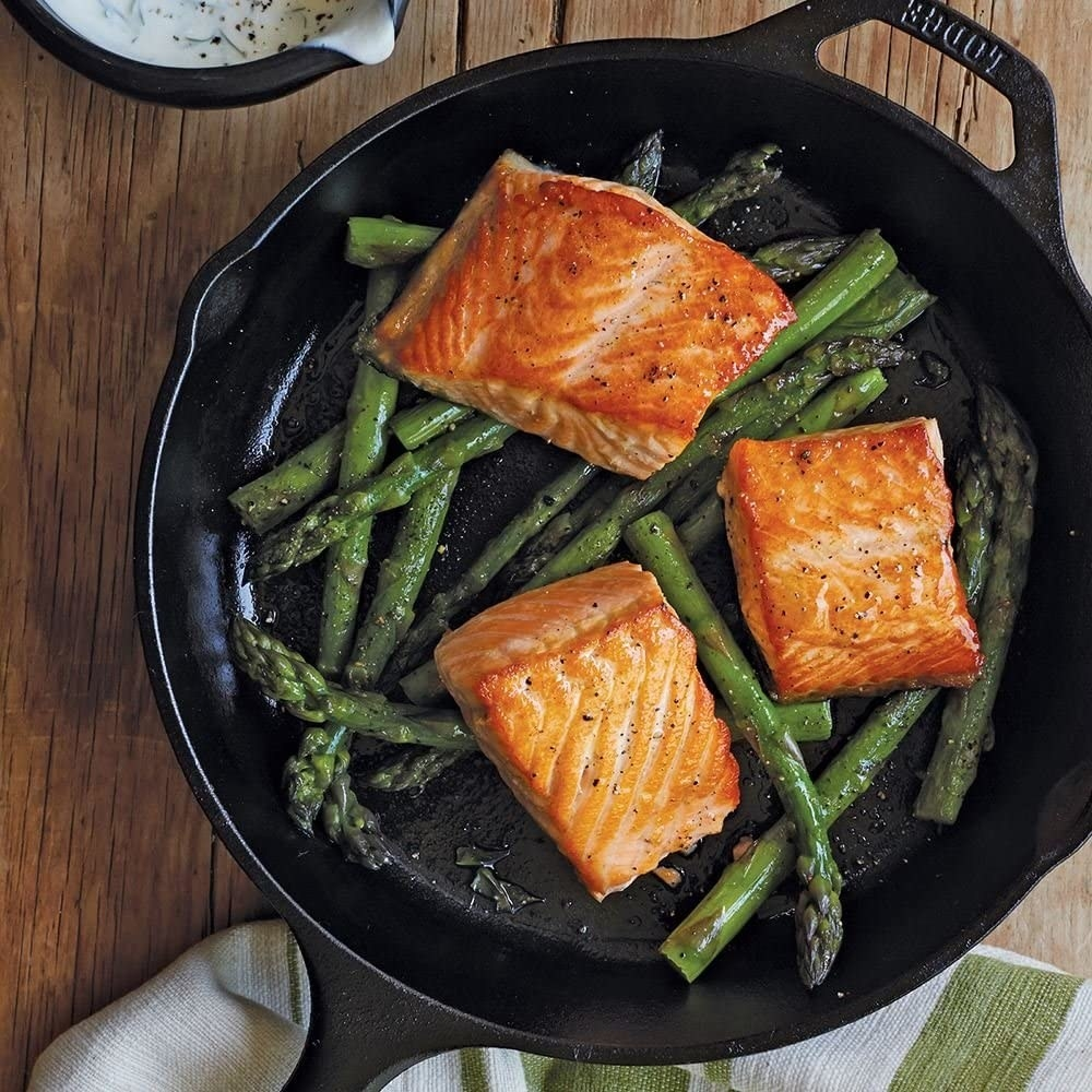 Black cast-iron skillet filled with salmon and asparagus