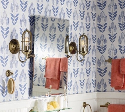 A bathroom with blue and white wallpaper and red towels