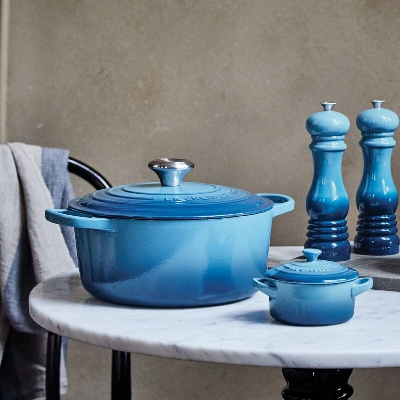 Blue dutch oven pots on a table top with blue salt and pepper shakers