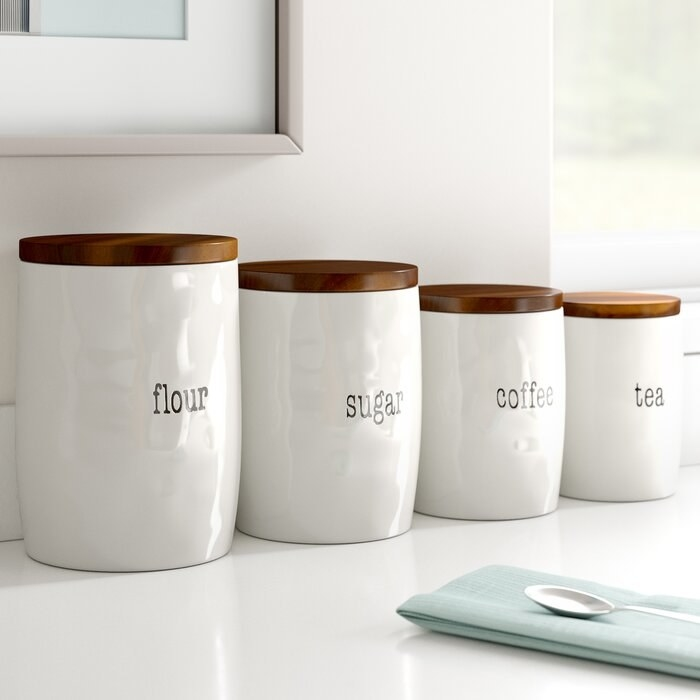 four white containers with wood lid labeled with flour, sugar, coffee, and tea