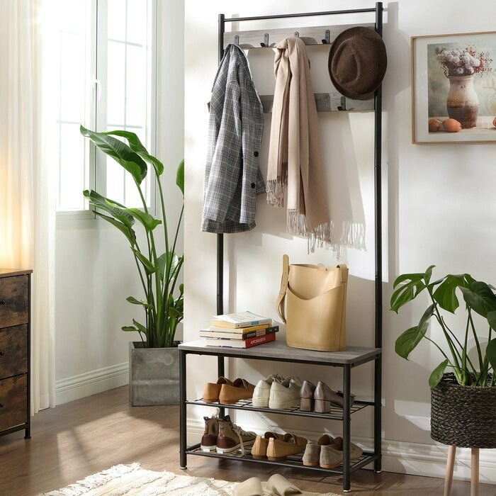 greige storage rack with shoes, coats, bags, hats, and books on it