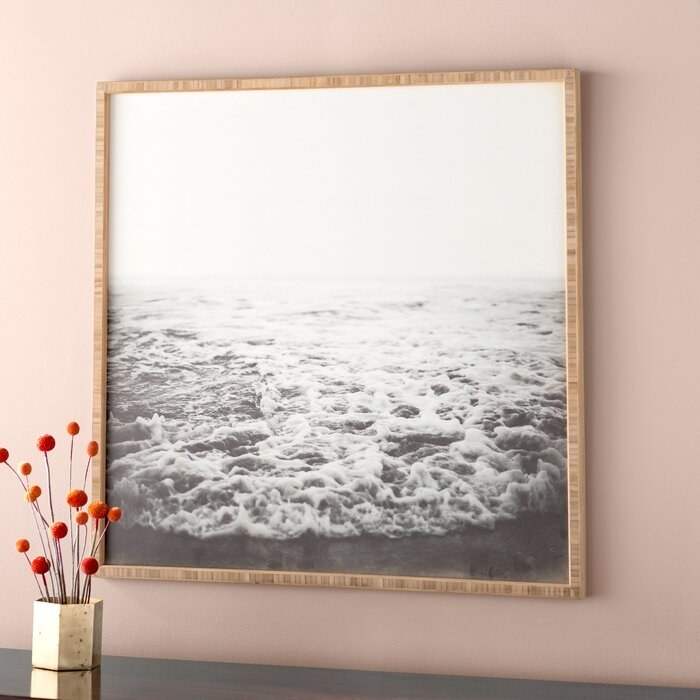 black and white photo of a wave crashing on a beach framed on a pink wall