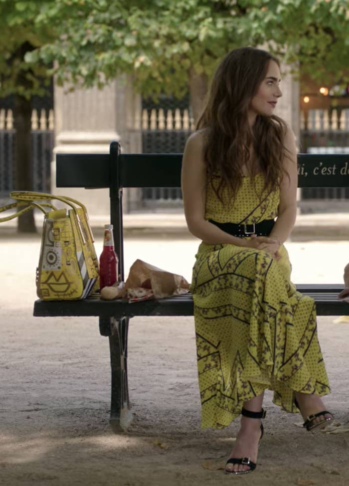 Emily sits on a park bench wearing a yellow and black patterned flowy maxi dress belted at the waist with black strappy heels