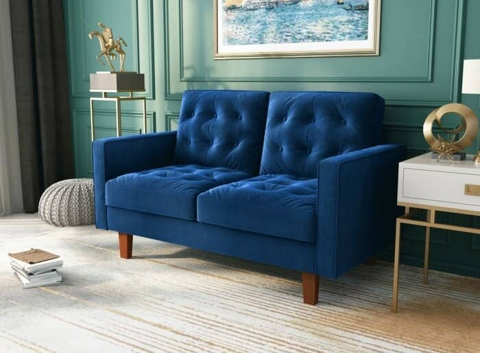 blue loveseat with tufted cushions