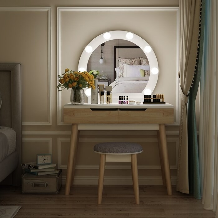 wood vanity with hollywood-style LED bulbs around a round mirror. A gray stool sits below the vanity
