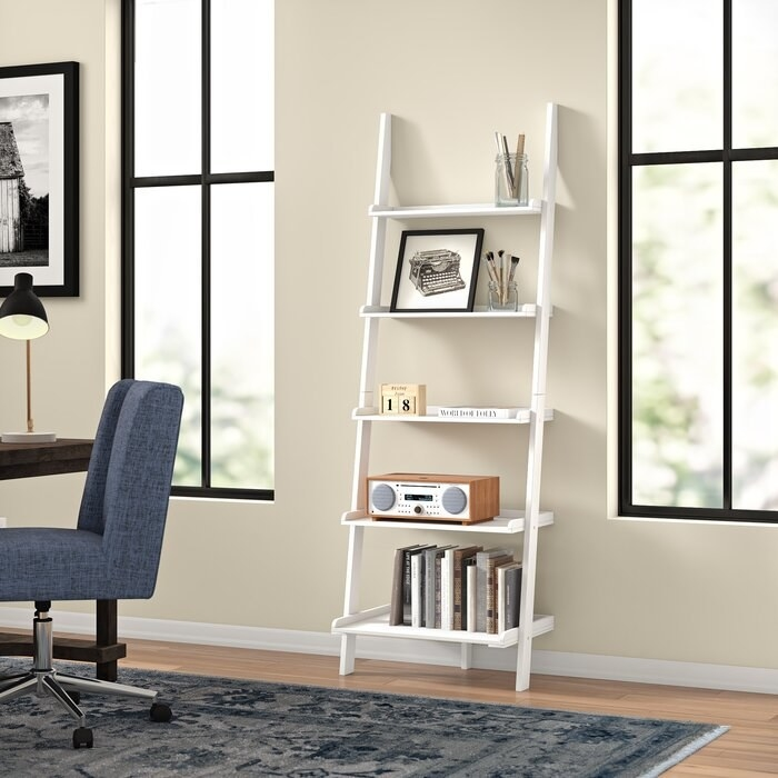 white ladder bookcase with books and knick knacks on it