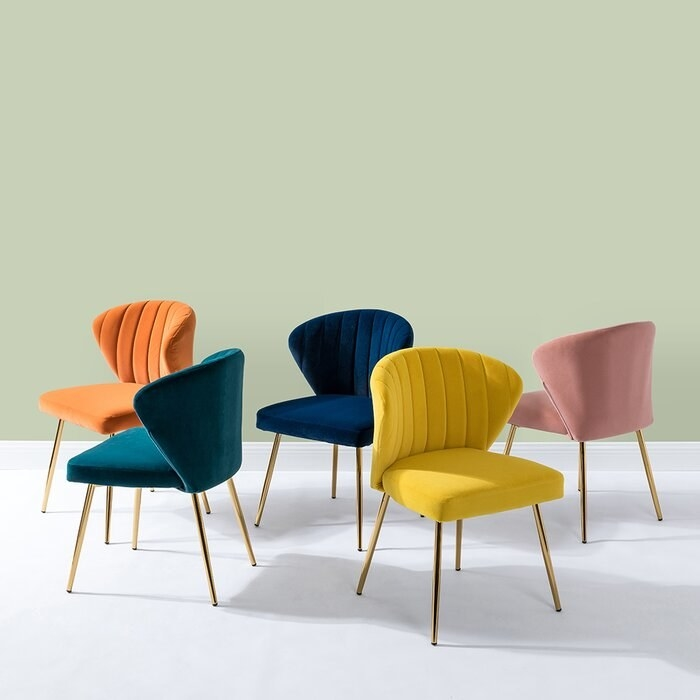 five different accent chairs in orange, navy, pink, yellow, and teal