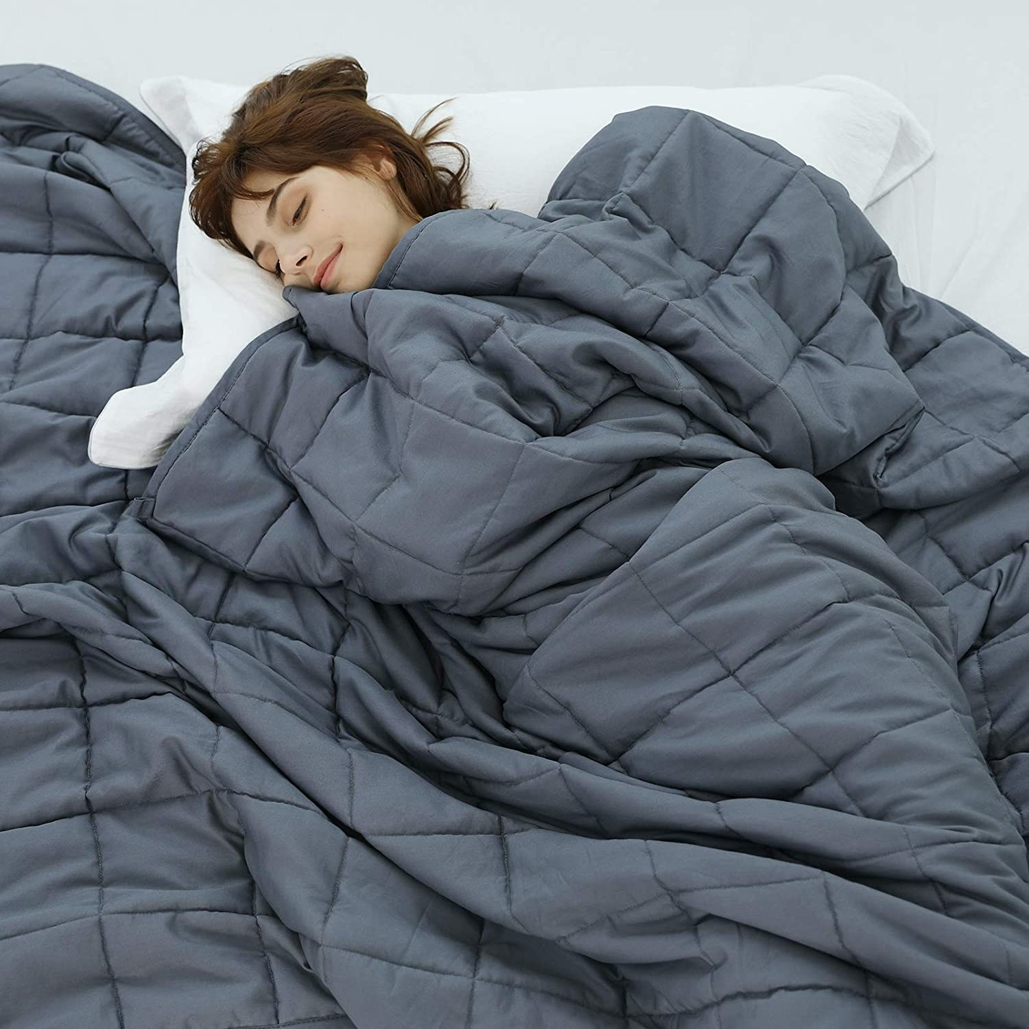 Model sleeping under the gray quilted blanket