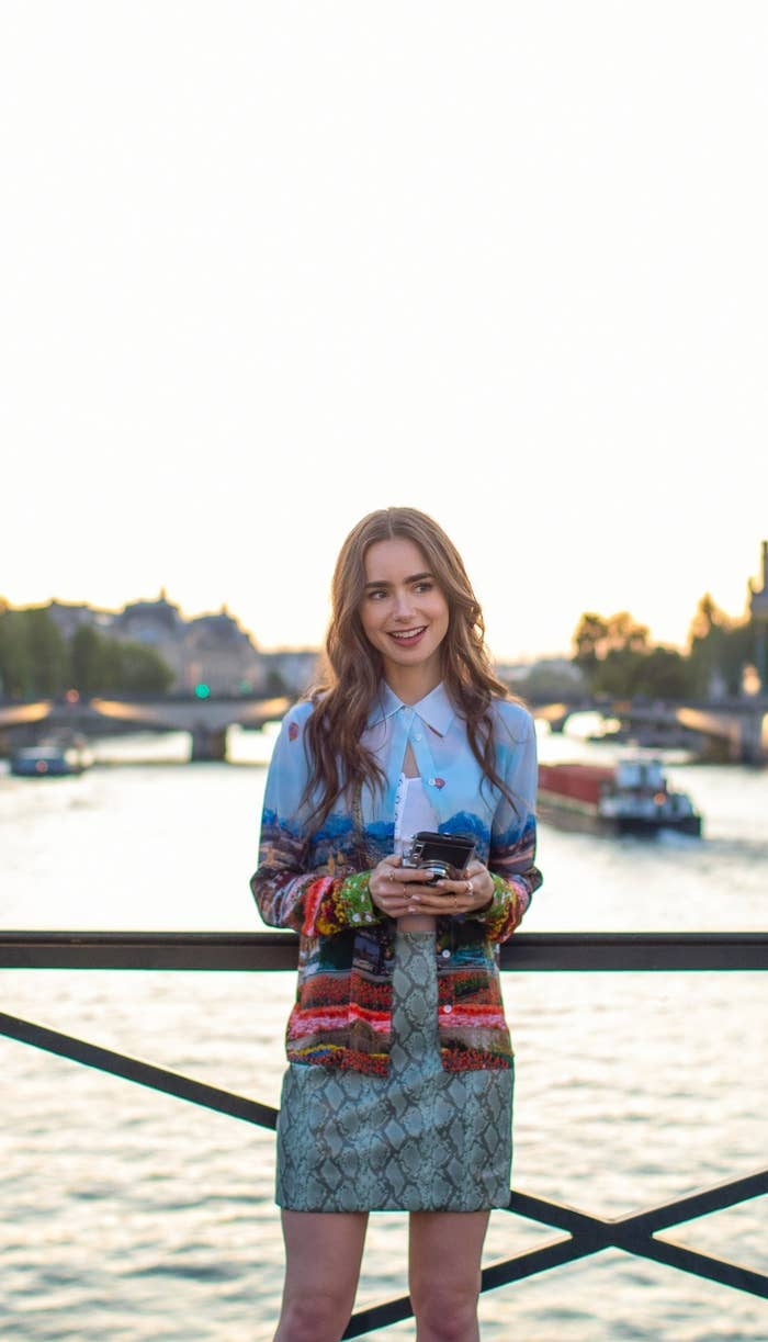 Emily stands on a bridge in front of the Seine wearing a snake print mini skirt and long sleeved Paris-motifed button up left open
