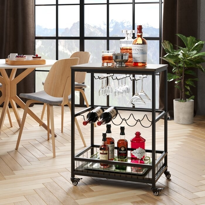 rolling bar cart packed with liquor bottles, wine bottles, and cocktail glasses