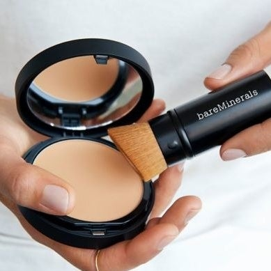 A person holding the foundation and brush set