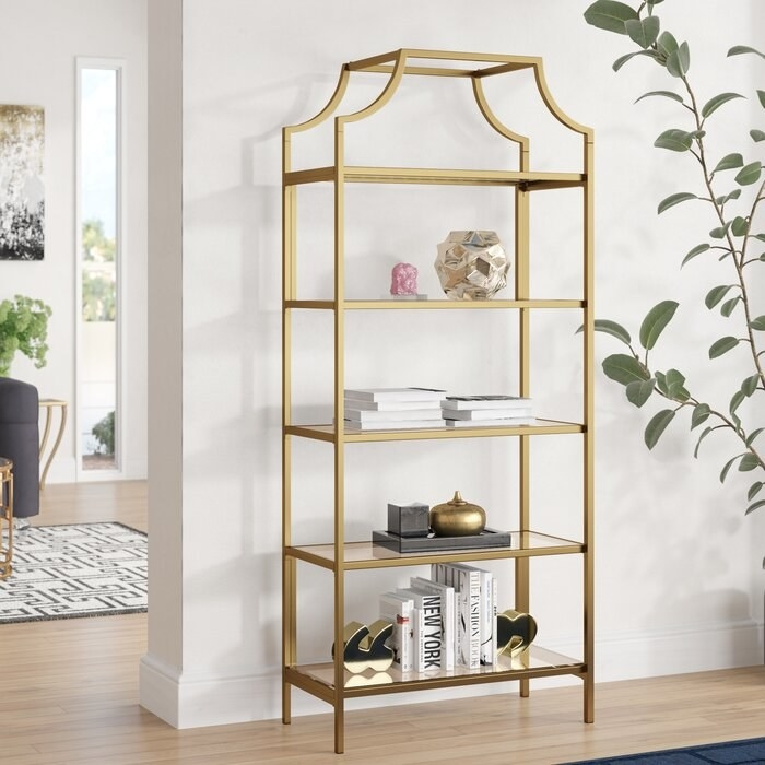 gold bookcase with books, sculptures, and bookends on it
