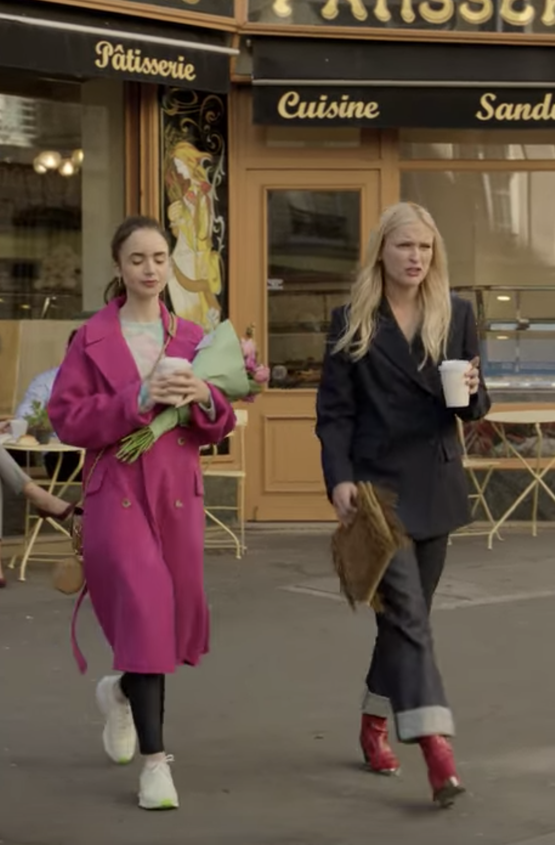 Emily and Camille walk out of a patisserie; Emily wears sneakers, black leggings, a pastel sweater, and a large pink coat