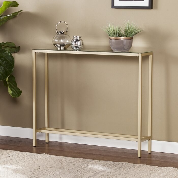 console table against a wall with golden legs