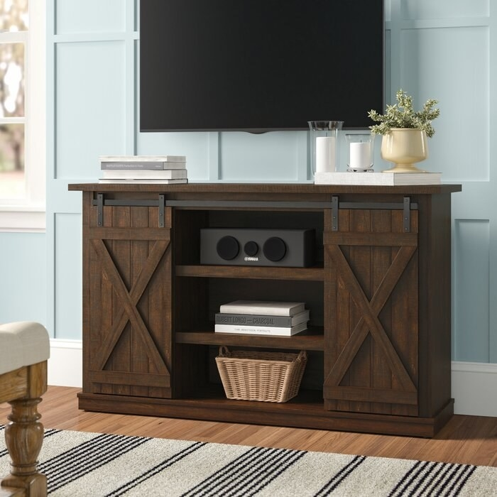 dark brown barn-style tv stand with a basket, books, and speaker in the middle shelves