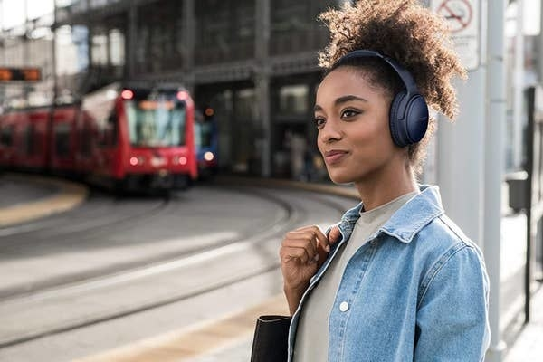 A person wearing the headphones while waiting for a train