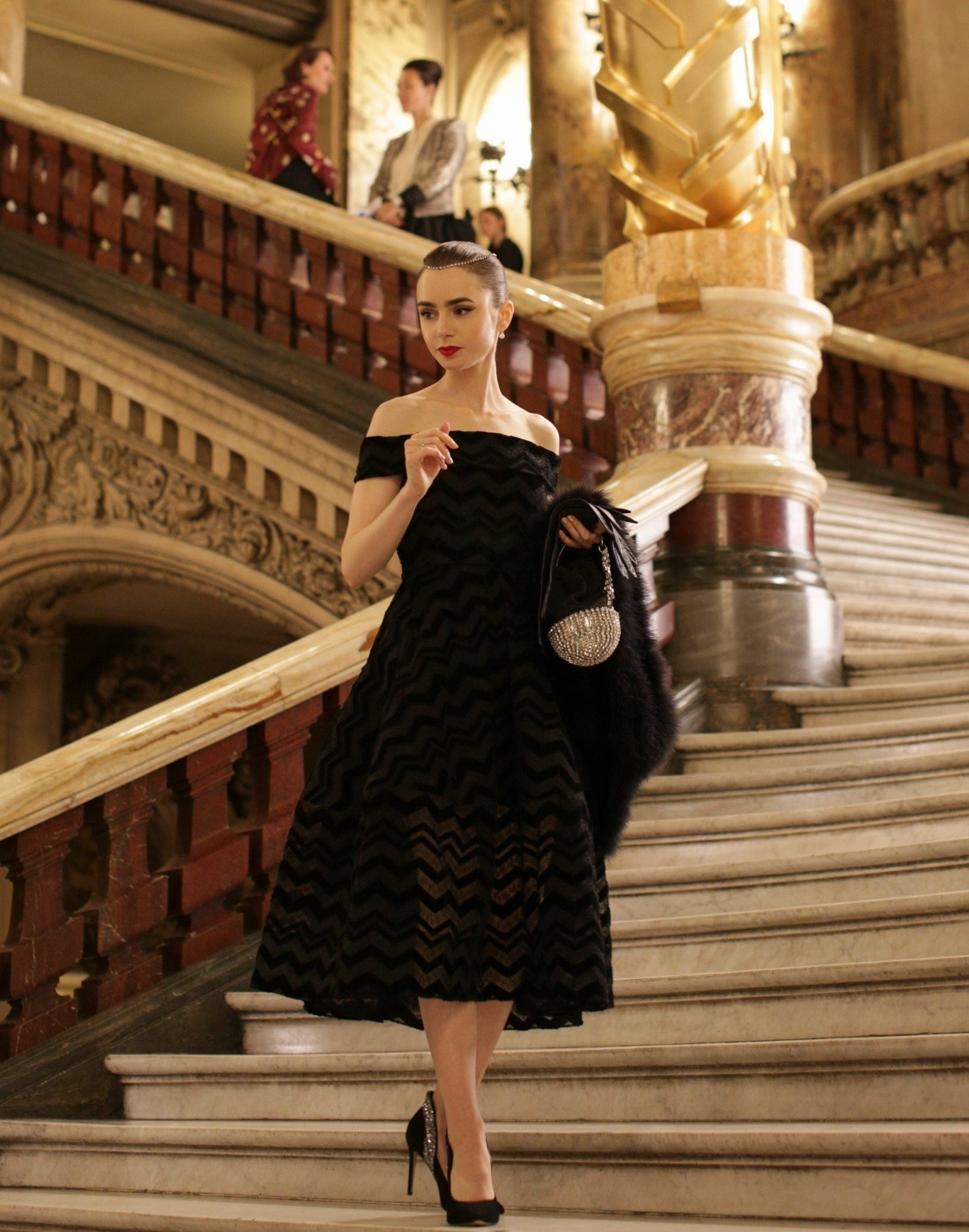 Emily stands on the steps of the operahouse in a black, off the shoulder midi dress with black heels and a diamond headband