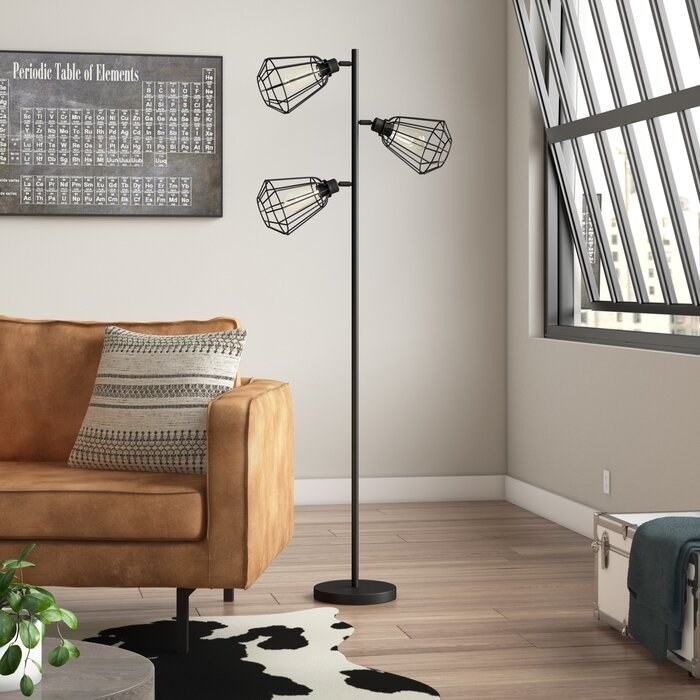 black floor lamp with three bulbs in a metal cage
