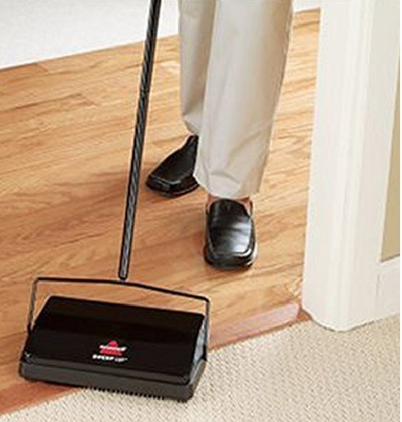 Model wearing black shoes using black black Bissell sweeper on beige carpet