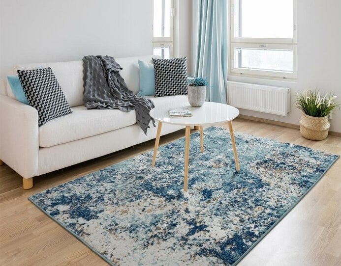 blue area rug in the middle of a living room under a coffee table