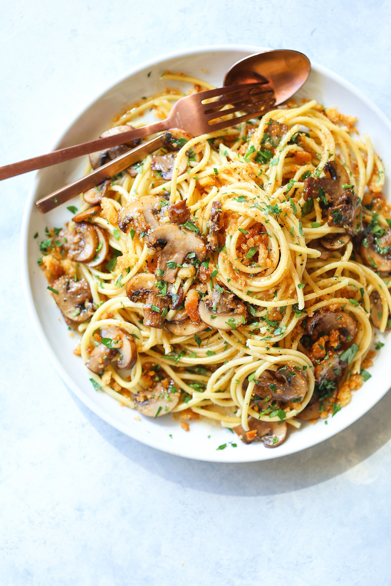 A plate of spaghetti with mushrooms, crispy bacon, and fresh herbs.