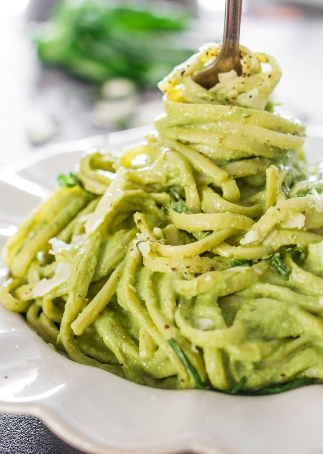 A fork twirling spaghetti in creamy spinach and avocado sauce.