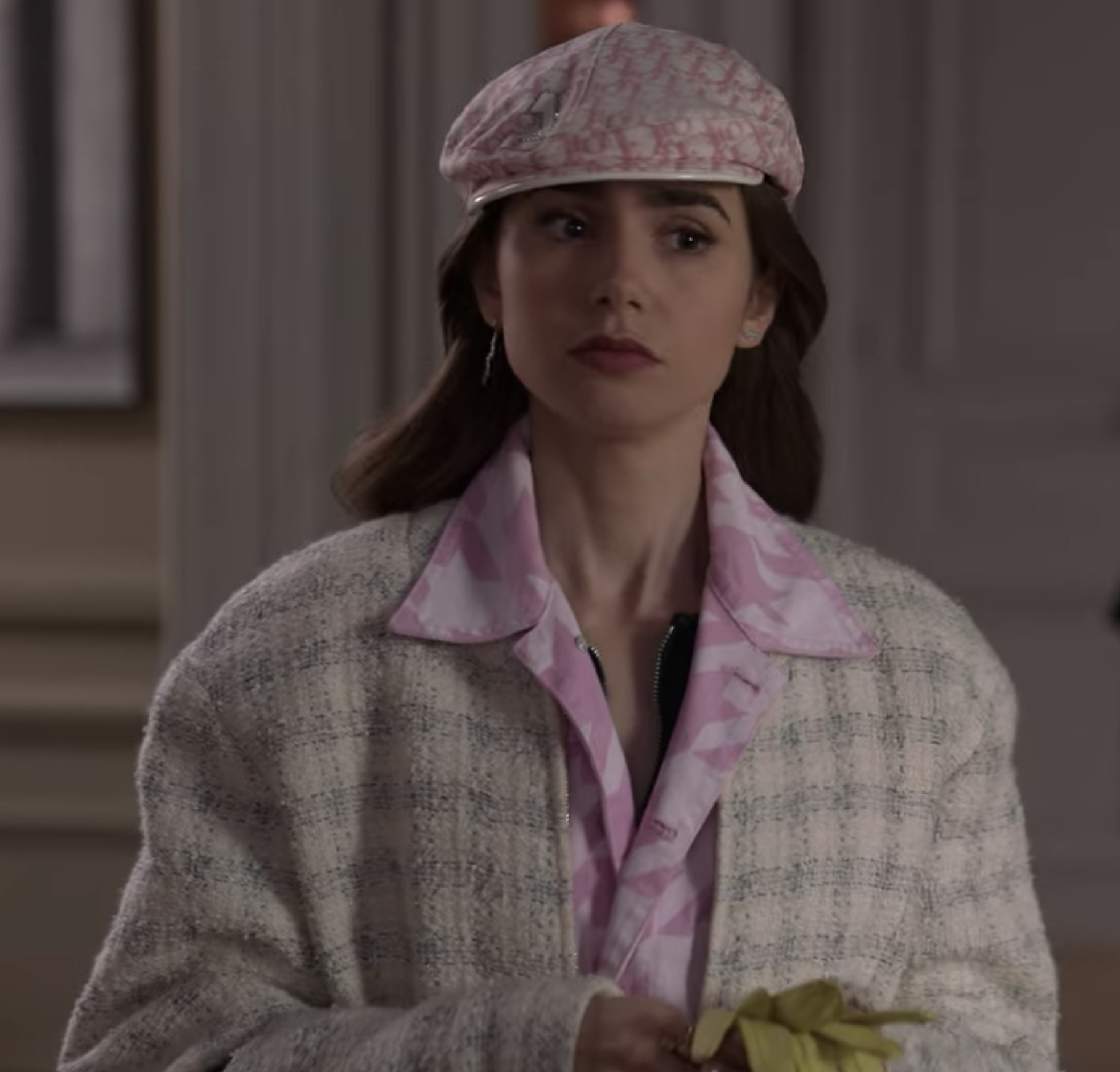 Emily wears a pink and white golf hat, a pink camo button up with the collar poking out over a pale pink plaid-like patterned coat