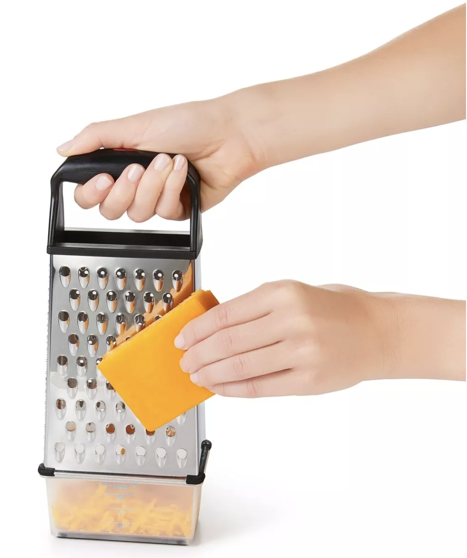 a person grating cheddar cheese with a box grater
