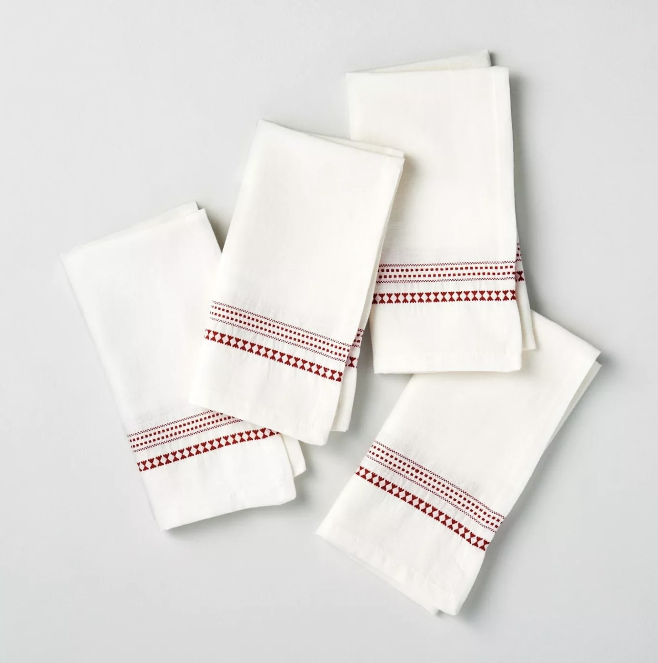four kitchen linens with red stripes and red checkered stripes