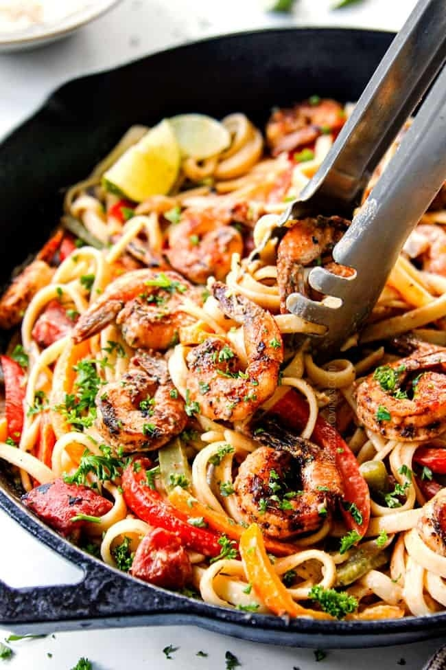 Tongs taking a serving of spicy Cajun shrimp pasta with peppers and herbs from a cast iron skillet.