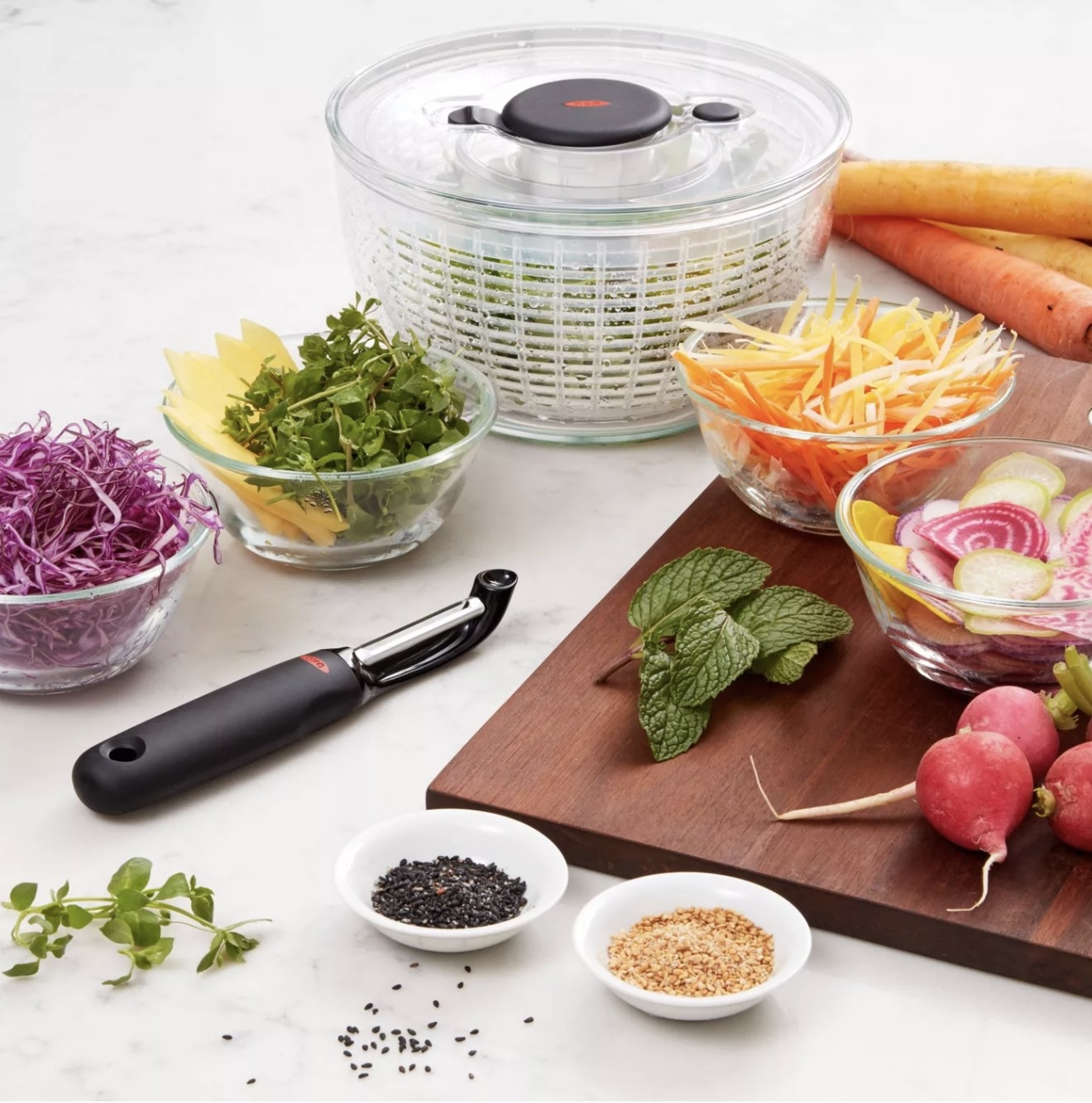 an oxo salad spinner holding salad on a counter next to an assortment of vegetables