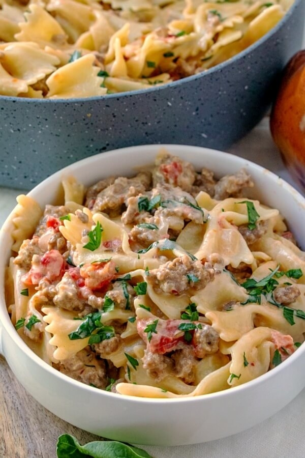 A bowl of bowtie pasta in a creamy sauce with crumbled sausage, tomatoes, and basil.