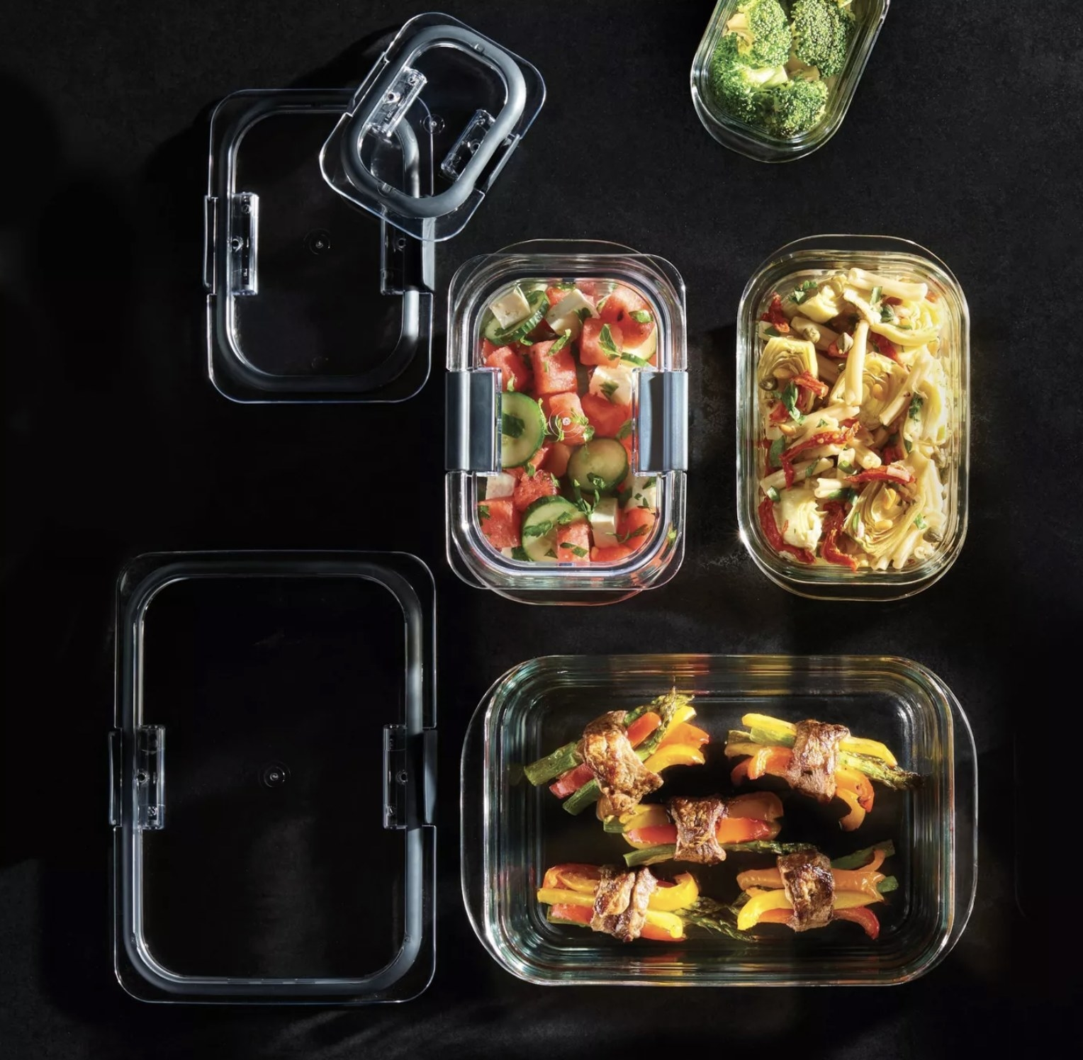 four glass food storage containers holding leftover food