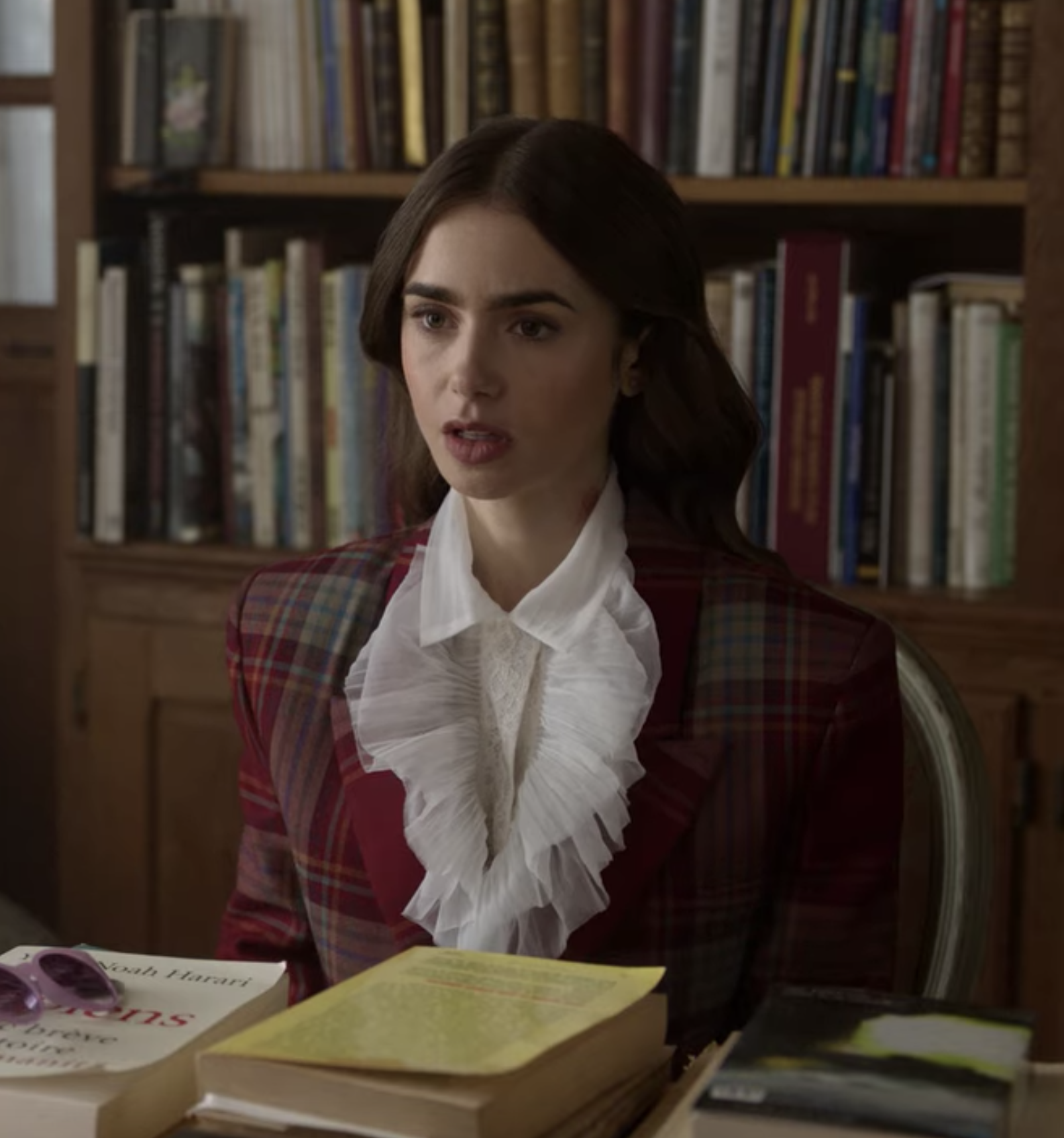 Emily sits at a desk wearing a plaid structured blazer over an extremely frilly white button up blouse